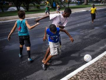 Niños jugando al fútbol en la calle