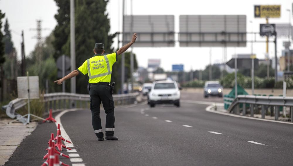 Un agente de la Guardia Civil de Tráfico da el alto a un conductor en un control