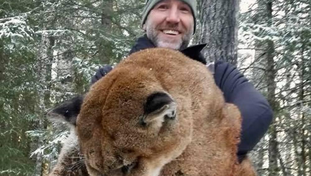 Steve Ecklund junto con el puma que ha cazado