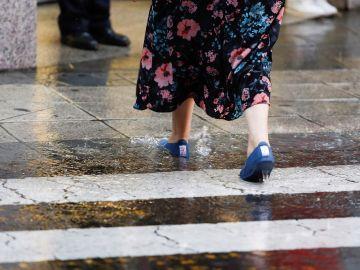 Una mujer cruza por un paso de peatones bajo una fuerte tormenta (Archivo)