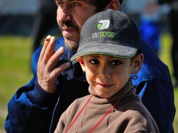Un niño junto a un adulto fumando
