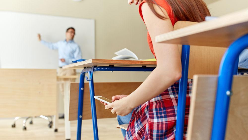 Niña consultando su teléfono en el aula