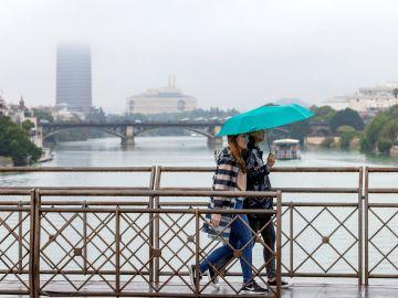 Dos personas atraviesan el puente de San Telmo, con el puente de Triana y Torre Sevilla.