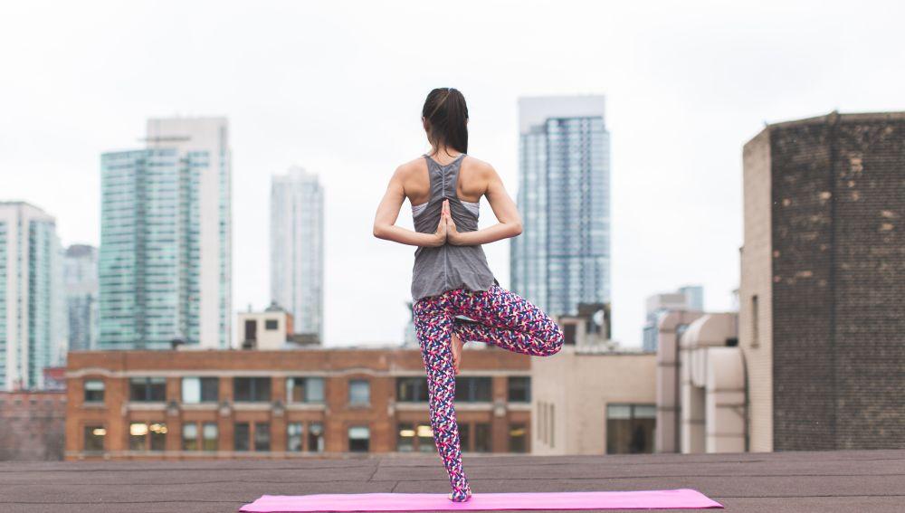 Mujer practicando yoga en una azotea