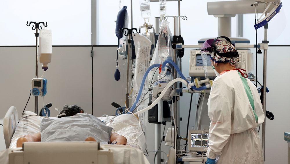Una enfermera del Complejo Hospitalario de Navarra atiende a un paciente ingresado en la UCI
