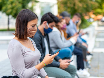 Grupo de jóvenes mirando el móvil con mascarilla