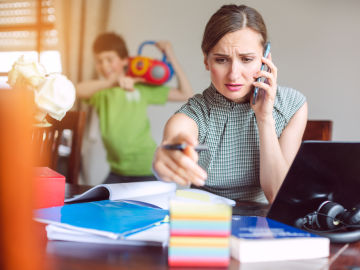 Mujer teletrabajando con sus hijos en casa