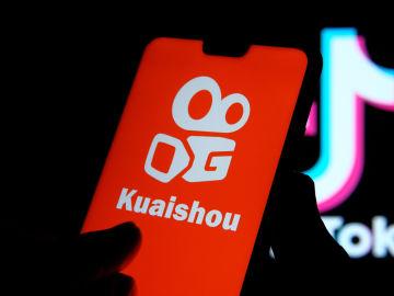 Un móvil muestra la portada de la app Kuaishou, al fondo aparece el logo de Tiktok