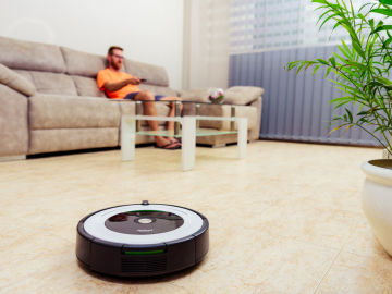 Un joven mira la televisión en el salón de su casa mientras un robot aspirador recorre el suelo