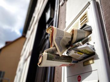 Periódicos acumulados en una puerta sugieren que alguien lleva tiempo sin pasar por casa.