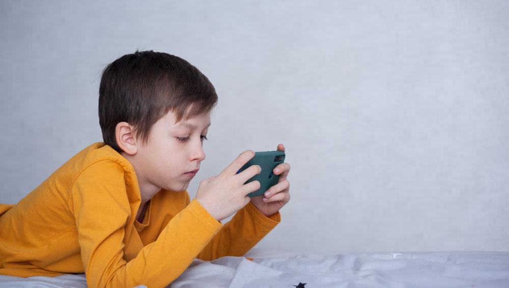 Un niño tumbado juega a un videojuego en su móvil