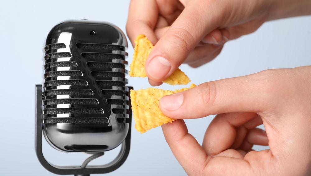 Unas manos rompen un snack cerca de un micrófono