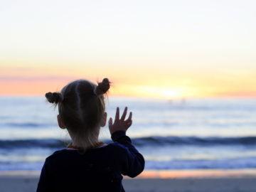 Una niña se despide del sol en una playa