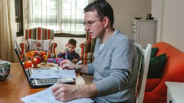 Un hombre teletrabaja desde casa mientras su hijo juega