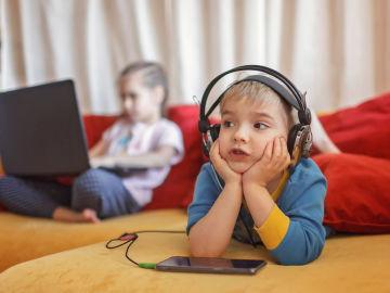 Dos niños usando dispositivos tecnológicos