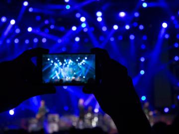 Una persona graba con su móvil un concierto.
