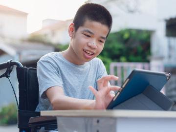 Chico con discapacidad maneja una tableta.