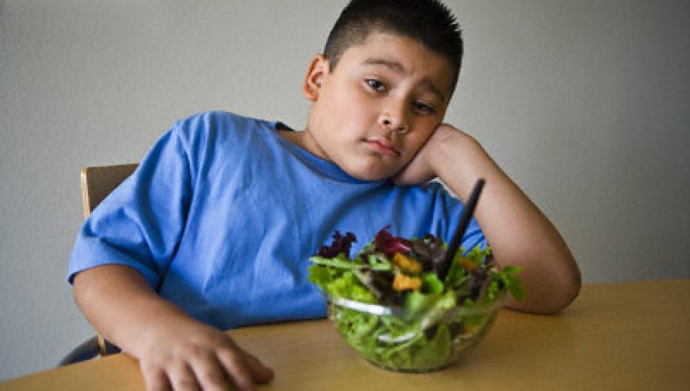Niño obeso con una ensalada
