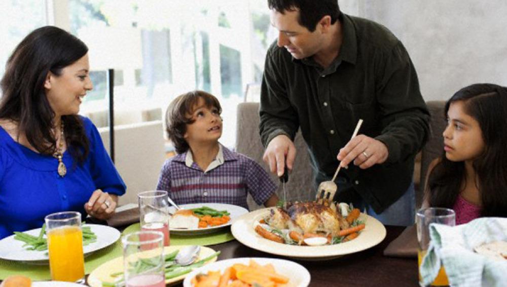 Unos padres sirven comida a sus hijos