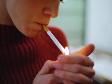 Una mujer encendiendo un cigarrillo