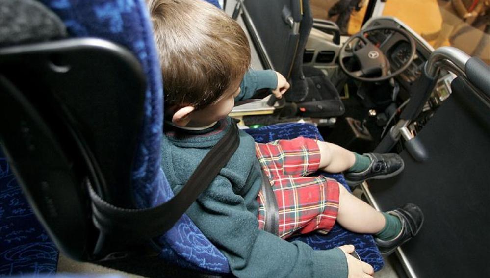 Menor con cinturón de seguridad en un autobús escolar