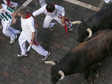 Mozos corren en la calle Mercaderes durante el segundo encierro