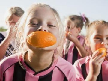 Niños practicando deporte y comiendo fruta
