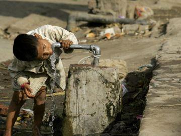 Niño bebiendo agua de una tubería