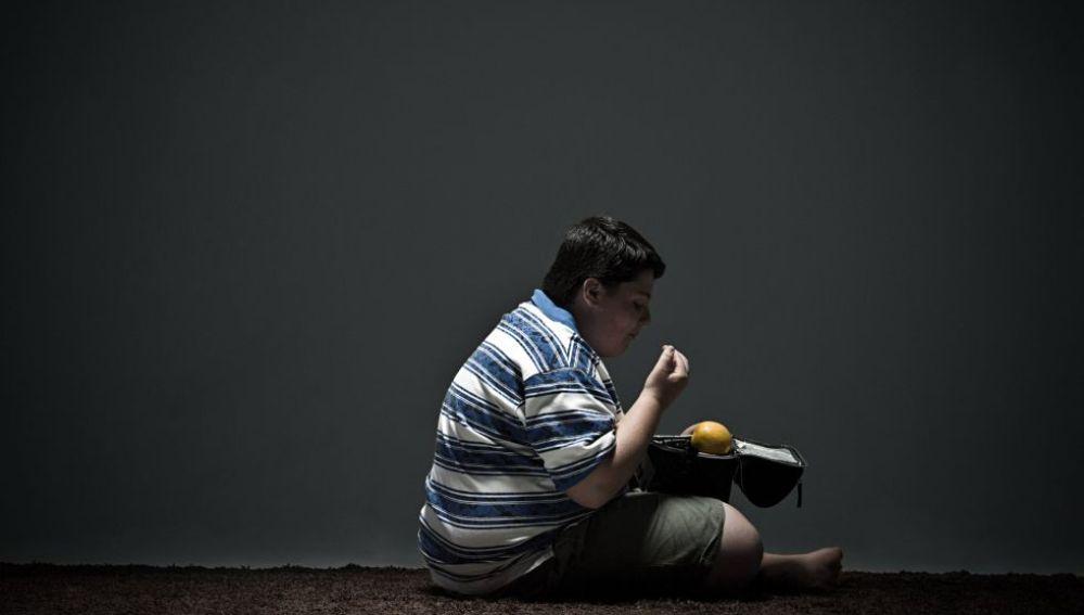 Niño con problemas de obesidad comiendo