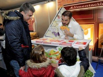 Un padre con sus hijos visita uno de los stands instalados en una carpa por el Día Mundial de la Diabetes