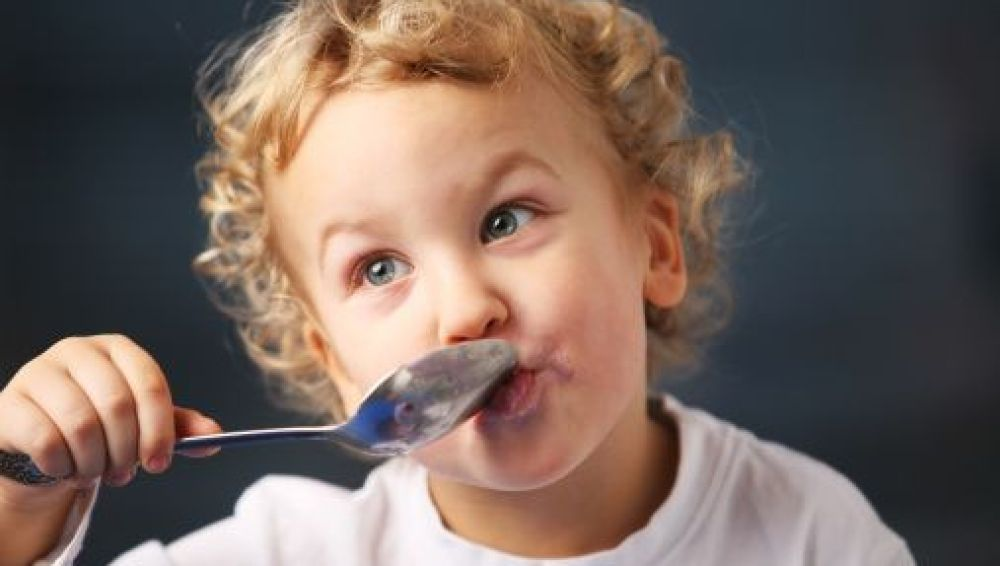 Un niño pequeño disfruta de un yogur