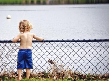 Un niño rubio mira un estanque