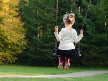 Una niña juega en un columpio