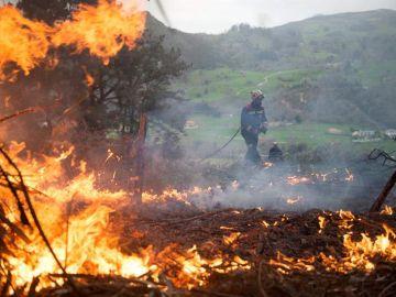 Un efectivo del Cuerpo de Bomberos de Cantabria durante las labores de extinción de un incendio forestal