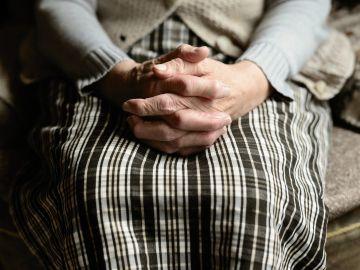 Una persona mayor se agarra las manos