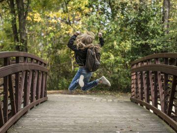 niña con mochila saltando en un puente