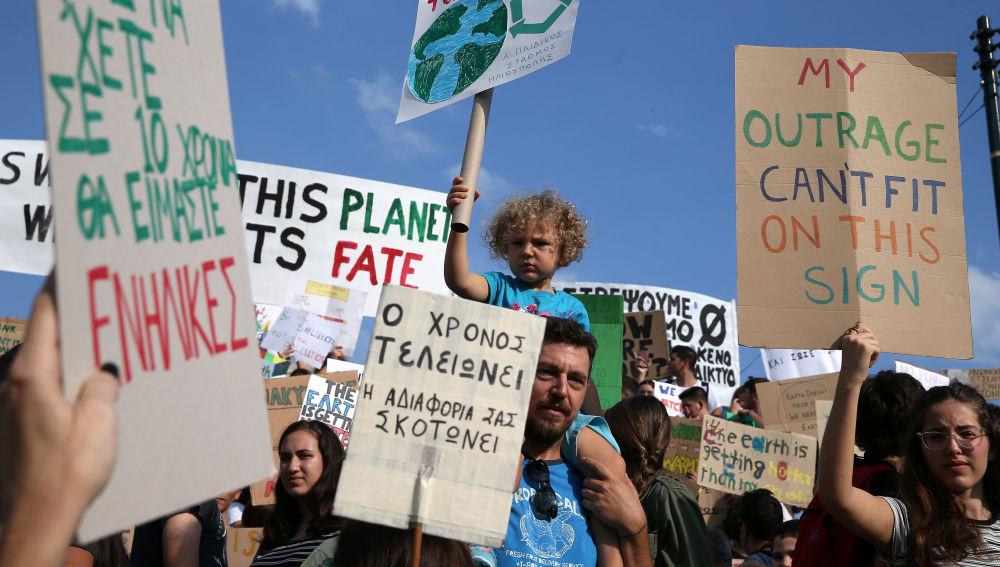 Un hombre lleva a un niño sobre sus hombros durante una manifestación de la Global Climate Strike del movimiento Viernes para el Futuro en Atenas