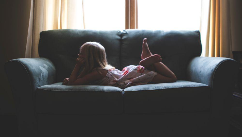 Niña tumbada en el sofá