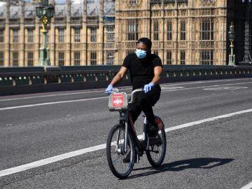 Un hombre con mascarilla circula en bicicleta frente al Parlamento británico en Londres