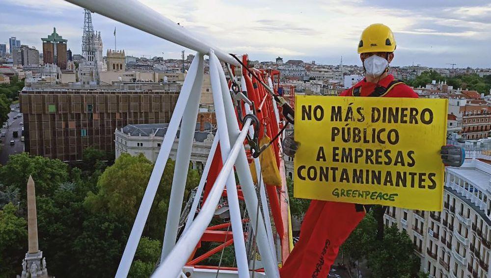 Vista de la pancarta desplegada por Greenpeace en la Plaza de Neptuno, en Madrid, para exigir que no se destine más dinero público a empresas contaminantes