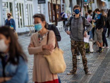 Una cola de gente con mascarillas en una calle de Italia