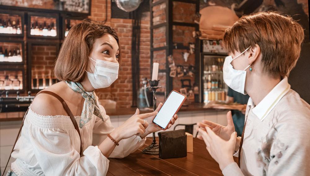 Dos jóvenes con mascarilla conversan en un bar mientras una sostiene un móvil