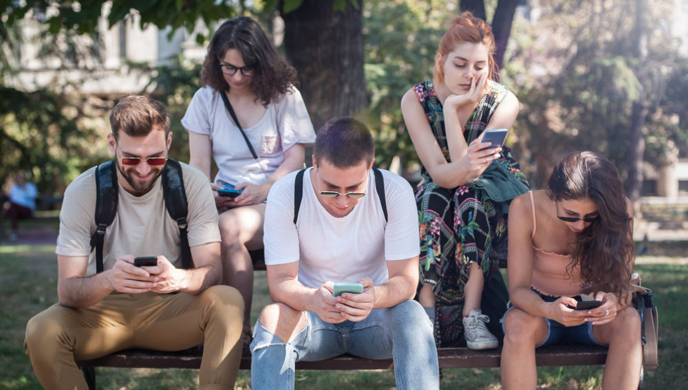 Grupo de amigos sentado en un banco miran sus móviles