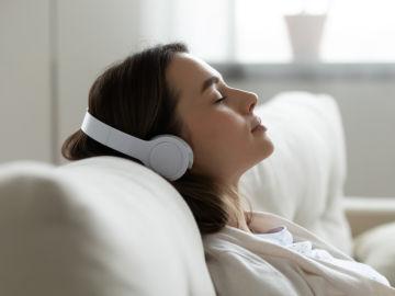 Mujer escucha tranquilamente sus auriculares en el sofá