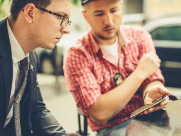 Un joven lee noticias de un móvil que sostiene otro