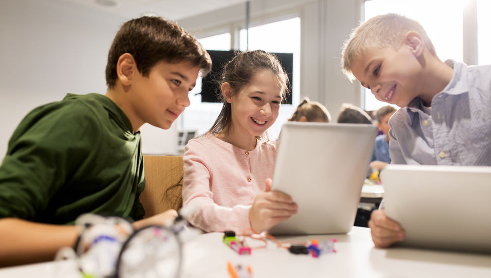 Dos niños y una niña juegan con tabletas en un campamento de verano