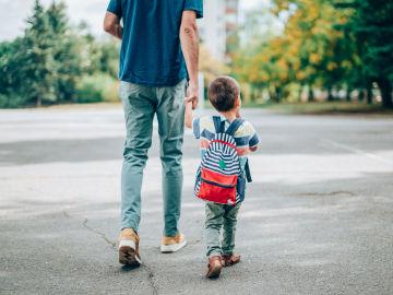 Un padre camina con su hijo en dirección al colegio