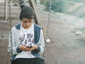 Un niño consulta su móvil en un parque