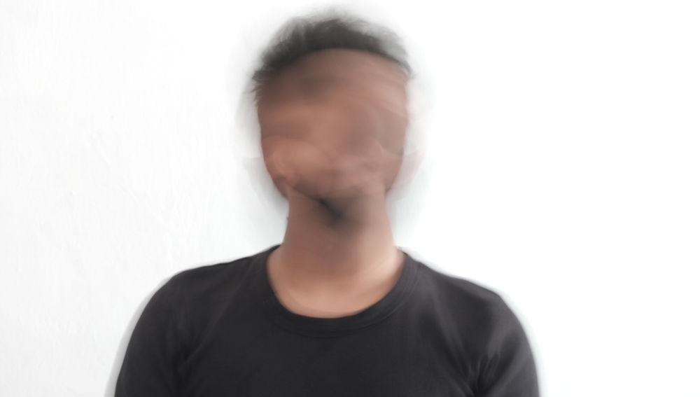 Imagen borrosa de la cara de un hombre joven.